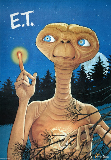 ET standing in a forest scene with his finger alight